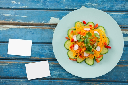 Digital composite of Bussiness cards on blue wooden desk with food 3d Stock Photo