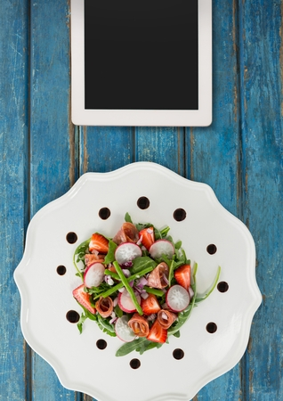 Digital composite of Tablet on blue wooden desk with food and copy space