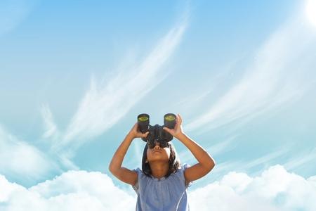 Digital composite of Girl looking through binoculars against sky