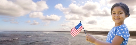 Digital composite of Girl with american flag against coastline Stock Photo