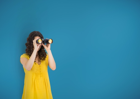 Digital composite of Woman looking through binoculars against blue background Stock Photo