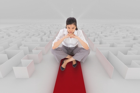 Digital composite of Woman sitting on a 3d maze with an arrow