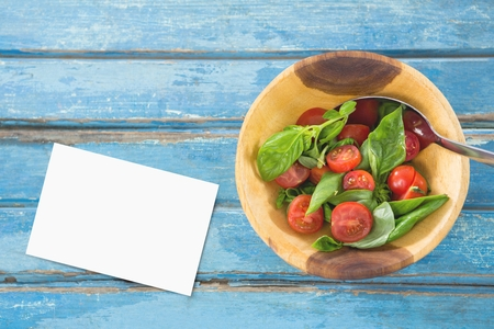 Digital composite of Bussiness card on blue wooden desk with food and copy space on paper Stock Photo