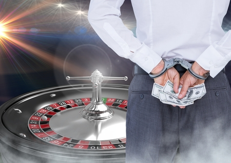 Digital composite of Man in hand cuffs with money and 3d roulette machine