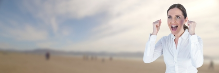 clenching: Digital composite of Business woman celebrating on blurry beach