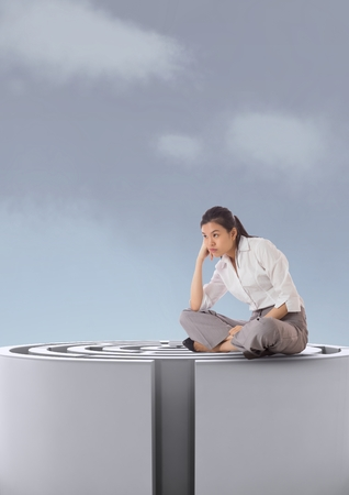 cross legged: Digital composite of Woman sitting on a 3d maze against a sky with clouds Stock Photo