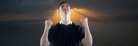 Digital composite of Man in jersey celebrating against water and dark clouds with sun rays Stock Photo