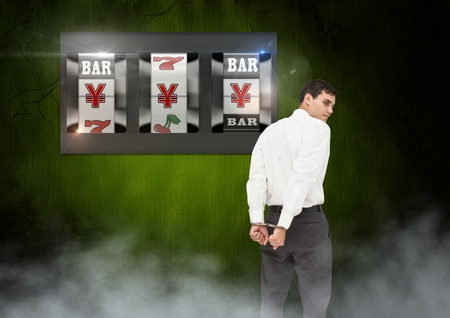 Digital composite of Back of Man Looking at 3d casino slot machine with hand cuffs Stock Photo