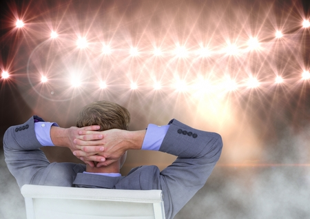 Digital composite of Seated man relaxed with flood lights