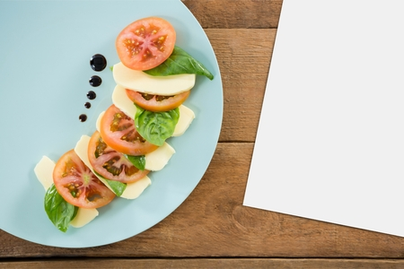 Digital composite of Blank card on wooden desk with food and copy space on a paper
