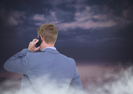 Digital composite of Back of Man Looking at clouds on phone Stock Photo