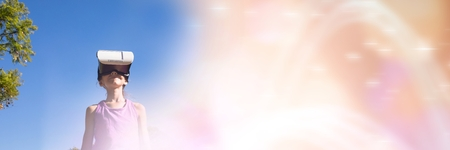 experiencing: Digital composite of Low angle of girl with virtual reality headset against sky with blurry peach transition