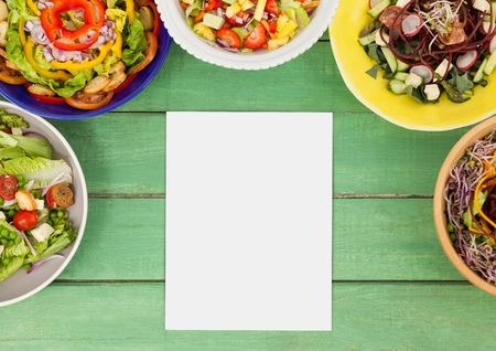 Digital composite of Blank card on green wooden desk with food and copy space on paper