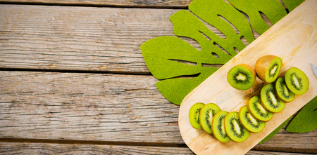 halved  half: Overhead view of kiwi slices on wooden cutting board Stock Photo