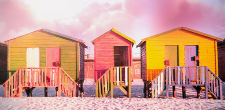 Scenic view of brown storm cloud against multi colored huts on sand against clear sky Stock Photo