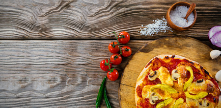 Overhead view of pizza by spices on wooden table Stock Photo