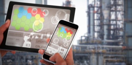 Close up of hands using digital tablet and 3D mobile phone against view of industry