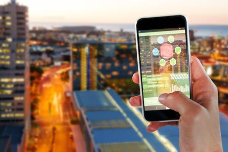 Imagen recortada de la mano que sostiene el teléfono inteligente 3D contra edificios iluminados por carretera en la ciudad Foto de archivo - 81069761