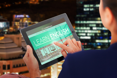 well dressed: Businesswoman working on digital 3D tablet over white background against glowing modern buildings in city