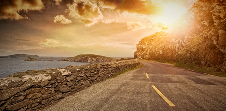 Empty road by sea against cloudy sky Stock Photo