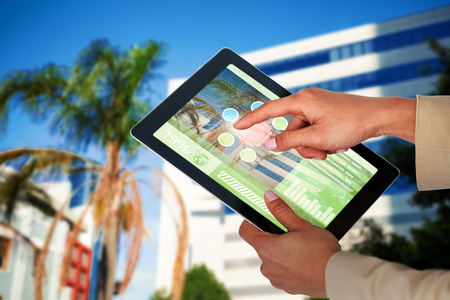 Businesswoman using digital 3D tablet against tree by glass building