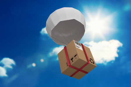 3D parachute carrying cardboard box against bright blue sky with clouds Imagens