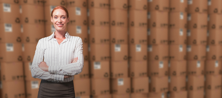 working attire: Female manager with arms crossed in warehouse against open cardboard box by pile of boxes