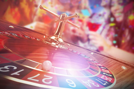 Happy friends with cocktails against 3d image of ball on wooden roulette wheel