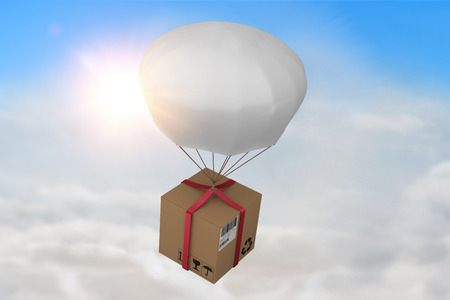 3D composite image of parachute carrying cardboard box against blue sky with white clouds