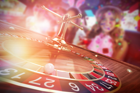 Portrait of female friends drinking cocktails against 3d image of ball on wooden roulette wheel Imagens