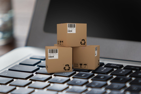 composite image: Illustration of cardboard 3D boxes against close up of laptop with glass of water