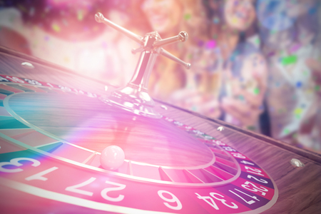Pretty girls holding champagne glass against 3D image of ball on wooden roulette wheel