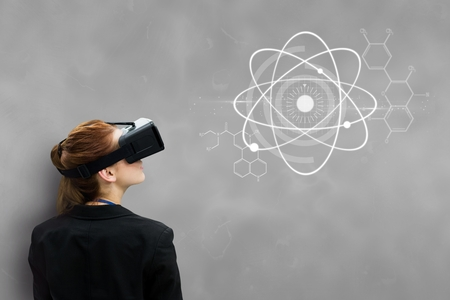 wireless: Digital composite of Woman in VR headset looking at interface against grey background Stock Photo