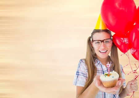Digital composite of Millennial woman with balloons and cupcake against blurry cream background