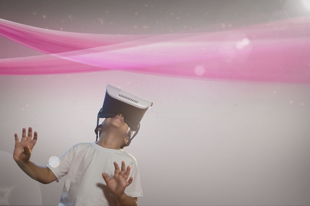 Digital composite of Boy with VR headset looking at a pink light against grey background Stock Photo
