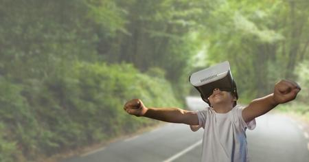 Digital composite of Boy in VR headset raising hands against road background