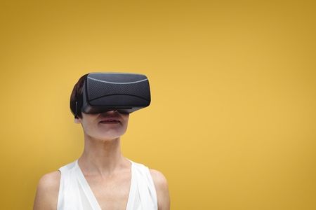 Digital composite of Woman in VR headset standing against yellow background