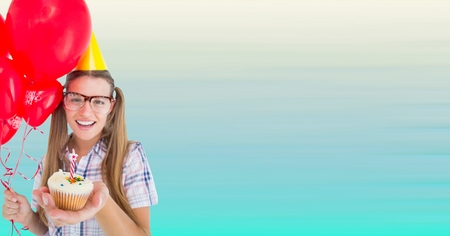 Digital composite of Millennial woman with balloons and cupcake against blurry blue background