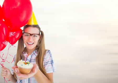Digital composite of Millennial woman with balloons and cupcake against blurry light grey background