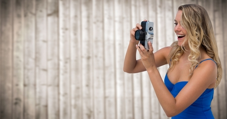 Digital composite of Millennial woman with camera against blurry wood panel