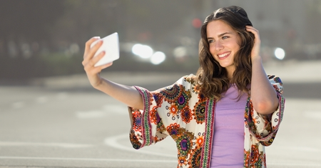 Digital composite of Millennial girl taking selfie against blurry street Stock Photo
