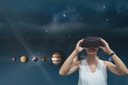 side viewing: Digital composite of Happy woman standing against sky background with flares and 3D planets Stock Photo