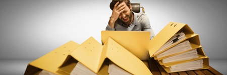 Digital composite of Stressed and tired man with lots of files table