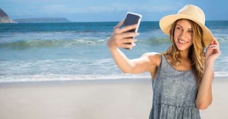Digital composite of Millennial woman in summer clothes taking selfie against beach Stock Photo