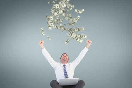Digital composite of Excited business man looking at money rain against blue background Stock Photo
