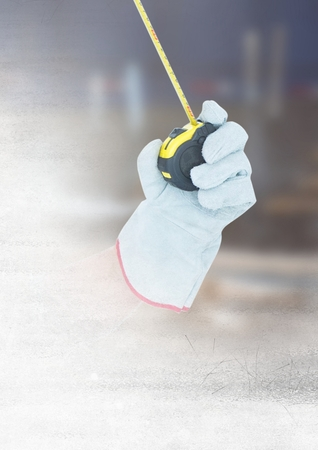 Digital composite of Hand with measuring tape on building site with transition effect