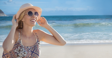 Digital composite of Woman with sunglasses and hat against beach