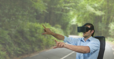 way out: Digital composite of Man in VR headset raising hands against road background Stock Photo