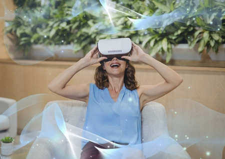 well dressed woman: Digital composite of Excited woman in VR headset looking at blue lights