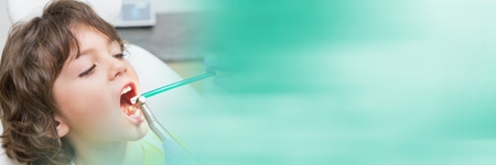 Digital composite of Close up of dentist working on boys mouth and blurry teal transition Stock Photo